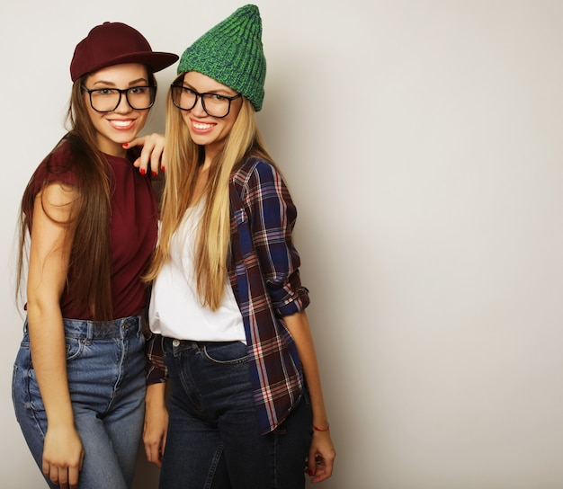 Ritratto di stile di vita ravvicinato di due amiche piuttosto adolescenti che sorridono e si divertono, indossano abiti hipster, occhiali e cappelli, umore positivo.