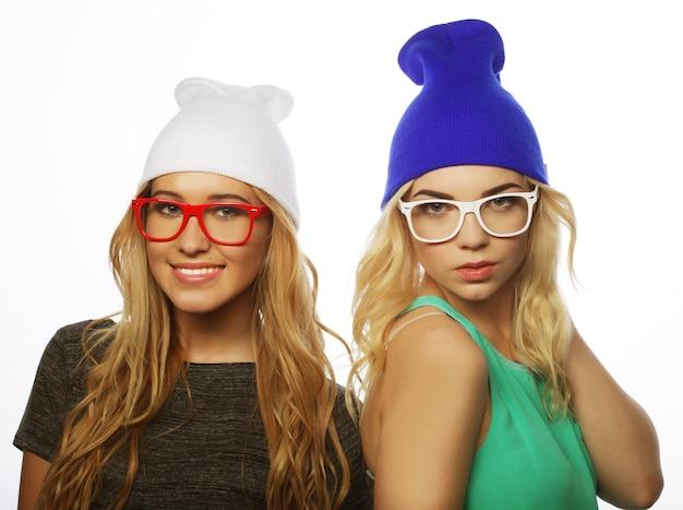 Ritratto di stile di vita ravvicinato di due amiche piuttosto adolescenti che sorridono e si divertono, indossano abiti hipster, cappelli e occhiali, umore positivo