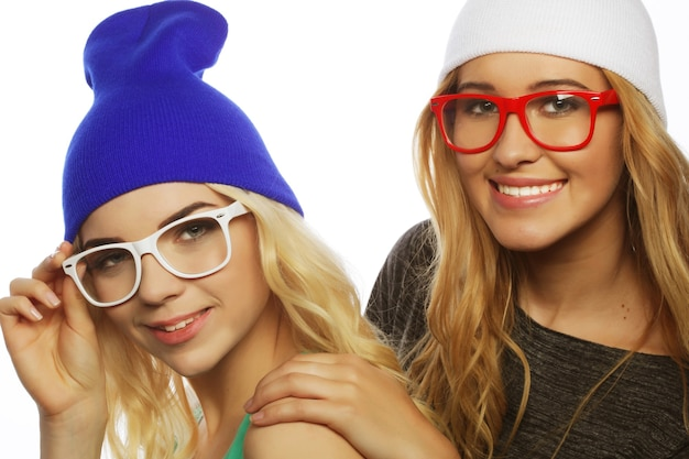 Ritratto di stile di vita ravvicinato di due amiche piuttosto adolescenti che sorridono e si divertono, indossano abiti hipster, cappelli e occhiali, umore positivo.