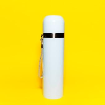 Primo piano del thermos blu-chiaro isolato sul giallo.