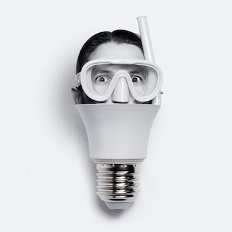 Close-up di lampadina con testa maschile indossando maschera subacquea, isolato su bianco.
