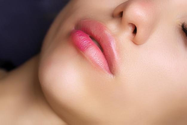 Primo piano delle labbra di una giovane modella che ha un tatuaggio sulle labbra composto al centro
