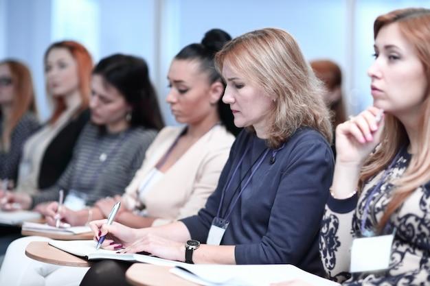 Primo piano. gli ascoltatori prendono appunti sui quaderni, seduti nella sala conferenze