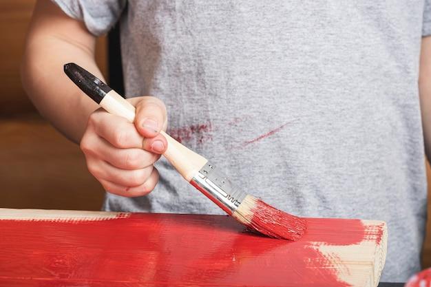 Primo piano di un ragazzino dipinge un albero con un pennello in mano in rosso