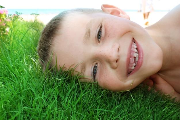 Primo piano sul ragazzino sorridente sull'erba