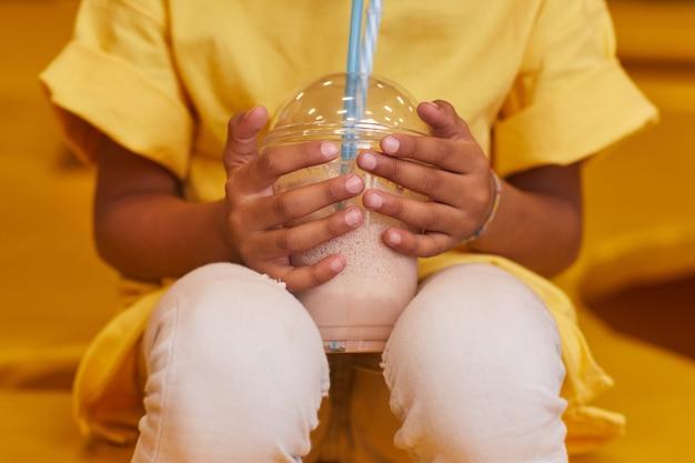 Primo piano del piccolo bambino che tiene il bicchiere con cocktail di latte e berlo dalla cannuccia