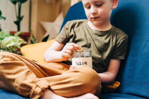 Primo piano delle mani del bambino ragazzo ragazzo che afferrano e mettono le monete della pila in un barattolo di vetro con salva