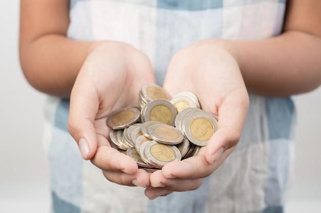 Primo piano delle mani della bambina che tengono le monete, il risparmio e il concetto bancario