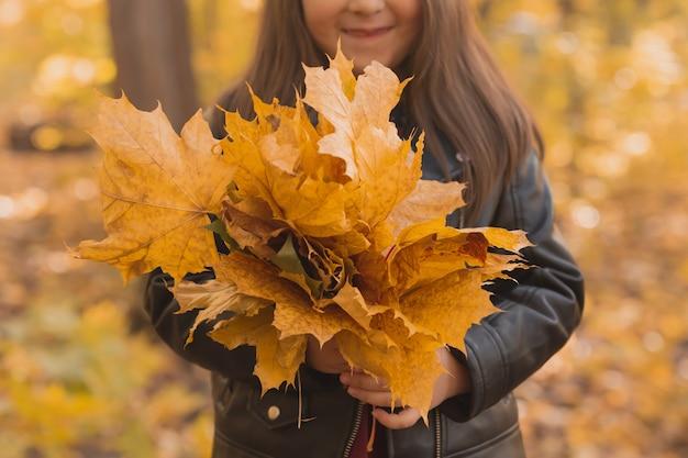 Il primo piano della bambina tiene un mazzo di foglie autunnali nelle sue mani nella stagione autunnale