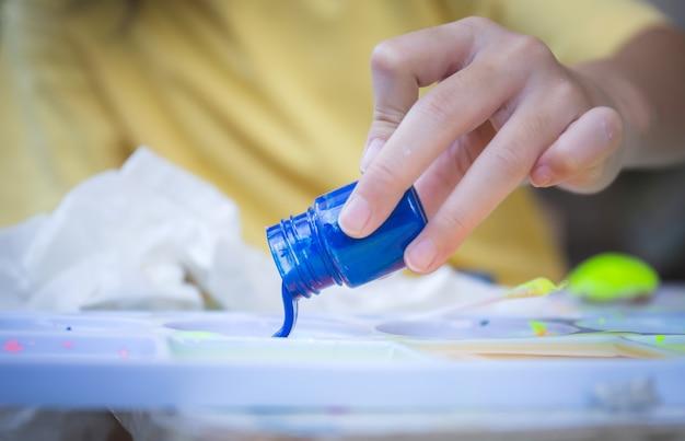 Chiuda in su della mano della bambina che versa inchiostro blu alla tavolozza, concetti di bambini di creatività