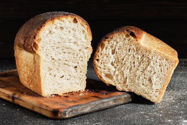 Primo piano su una pagnotta di pane bianco fresco rustico su un tagliere