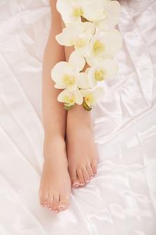 Primo piano di lunghe gambe femminili con perfetta pelle liscia e morbida e fiori