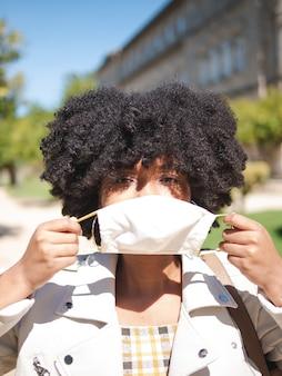 Sguardo da vicino di una giovane donna di colore con una maschera protettiva bianca per prevenire il coronavirus, all'aperto, isolata