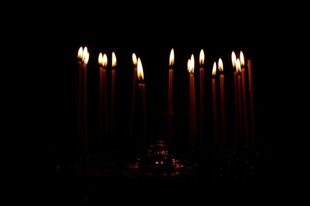 Chiudere un sacco di candele accese isolate su sfondo nero.
