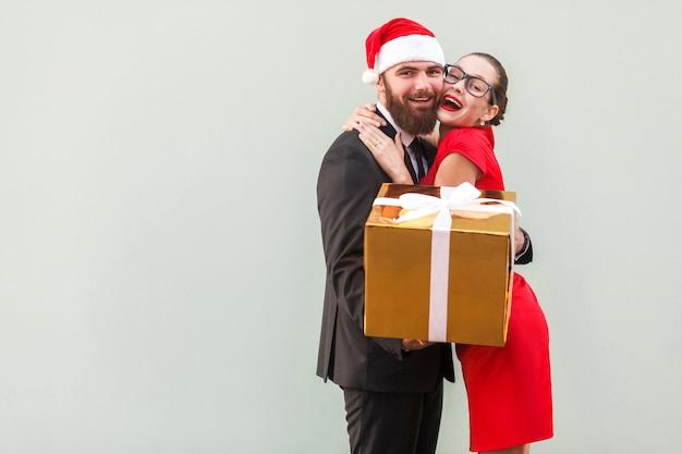 Avvicinamento. concetto di amore. bella ragazza che abbraccia uomo d'affari felice, perché ha dato regali. foto in studio, sfondo grigio