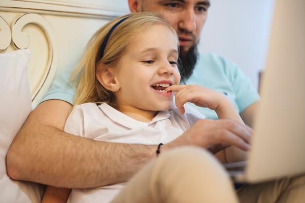 Chiuda in su di una bambina bionda adorabile che morde il suo dito sorridente mentre suo padre è choding cartoni animati sul suo laptop nel letto.