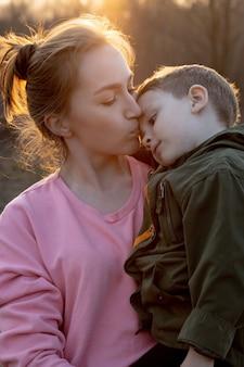 Chiuda in su di una madre adorabile e di suo figlio divertendosi all'aperto. piccolo bambino carino trattenuto da sua madre tra le braccia che sta ridendo contro il tramonto.
