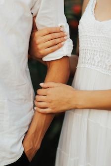 Primo piano delle coppie amorose mano nella mano all'aperto. mani e cuori insieme per sempre.