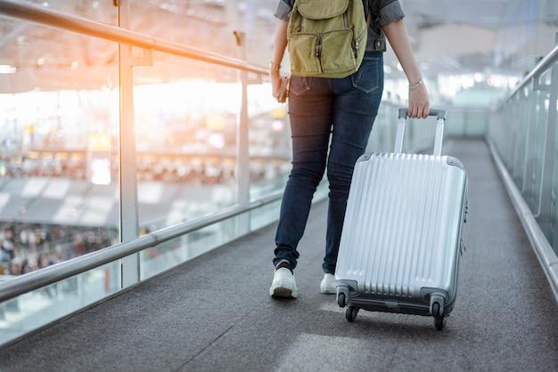 Chiuda sulla parte inferiore del corpo del viaggiatore donna con valigia bagagli andando in tutto il mondo