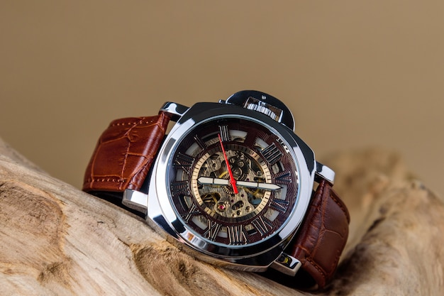 Chiuda su degli orologi di lusso dell'uomo disposti su legname nel fondo marrone