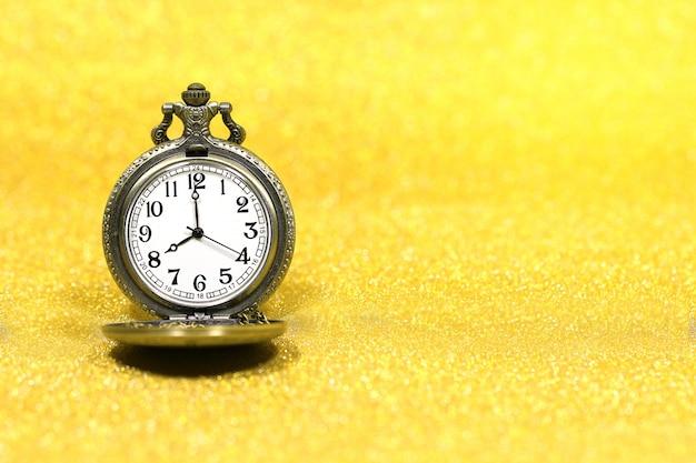 Chiuda su dell'orologio da tasca di lusso sul fondo di scintillio con lo spazio della copia