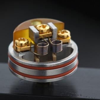 Primo piano, colpo a macroistruzione di doppia micro bobina in atomizzatore di gocciolamento ricostruibile di fascia alta per inseguitore di sapori, attrezzatura da svapo, fuoco selettivo