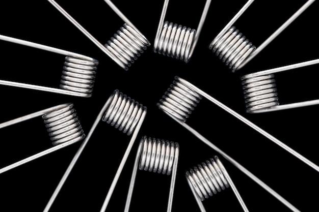 Primo piano, ripresa macro di micro bobine prefabbricate in senso antiorario isolate sullo sfondo nero della trama, per atomizzatore, atty, sigaretta elettronica, dispositivo di svapo