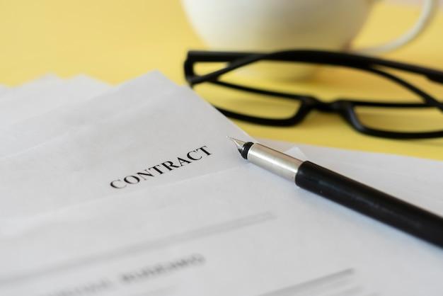 Una vista macro ravvicinata di un documento contrattuale con occhiali e una penna