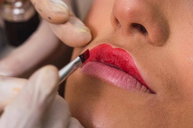 Chiuda in su delle mani di un artista di trucco che dipingono le labbra di una donna
