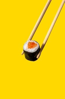 Primo piano maki roll con salmone su bacchette su sfondo giallo.