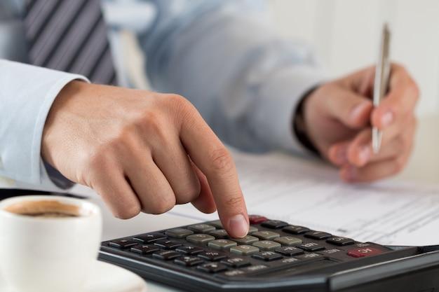Chiuda in su del ragioniere maschio o banchiere che calcola o controlla l'equilibrio. contabile o ispettore finanziario che fa rapporto finanziario. finanze domestiche, investimenti, economia, risparmio di denaro o concetto di assicurazione