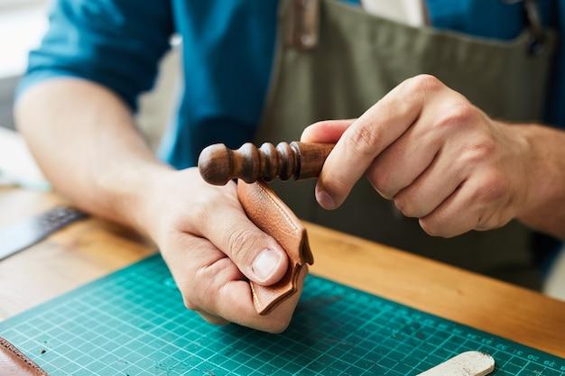 Primo piano del titolare della carta di pelle di finitura artigianale maschile nello spazio di copia dell'officina dei pellettieri