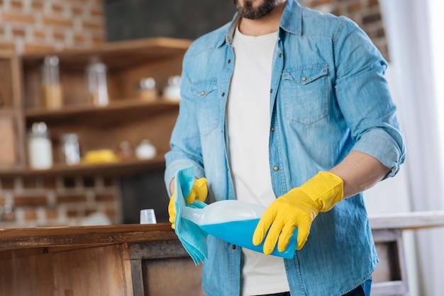 Primo piano del corpo maschile che trasporta detergente e panno per la pulizia mentre si veste i guanti