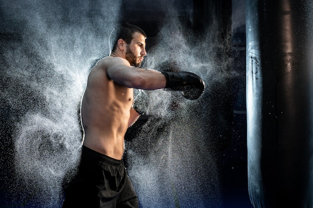 Chiuda in su boxer maschio boxe nel sacco da boxe, rallentatore.