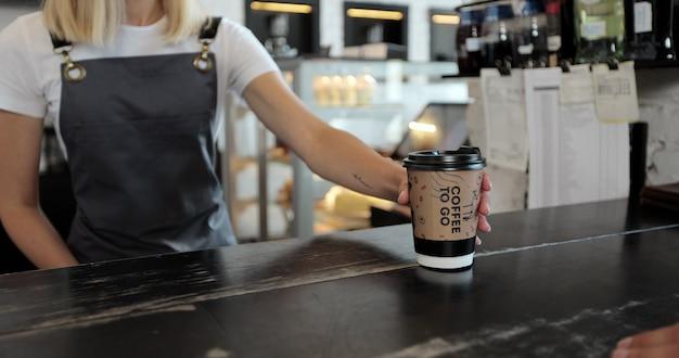 Il cliente maschio ravvicinato paga il caffè da asporto con la tecnologia di pagamento nfc senza contatto su smartphone al barista amichevole nel cliente utilizza il cellulare per pagare tramite il terminale bancario.