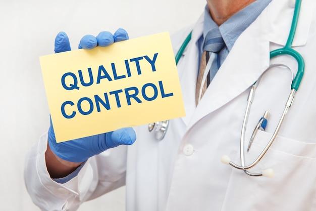 Primo piano di un medico maschio in guanti con un cartello con il controllo di qualità del testo