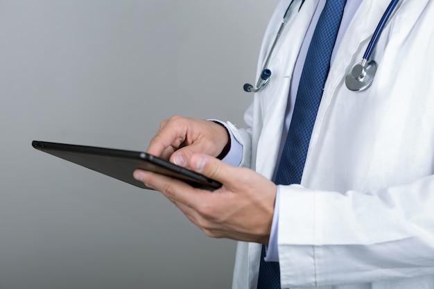 Primo piano delle mani del medico maschio che toccano pc digitale della compressa. sanità e concetto medico