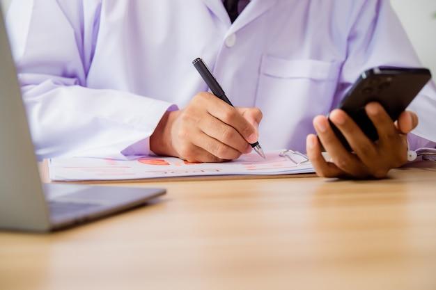 Primo piano di un medico maschio che utilizza uno smartphone mobile che lavora su un computer portatile in ospedale, una teleconferenza o un concetto di telemedicina.