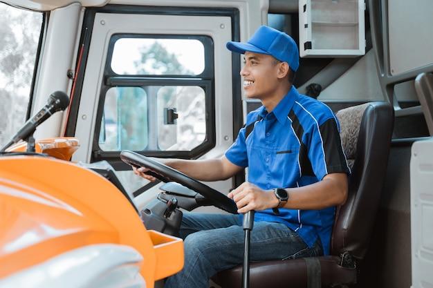 Chiuda in su di un conducente maschio in uniforme che tiene il volante e la leva del cambio nell'autobus