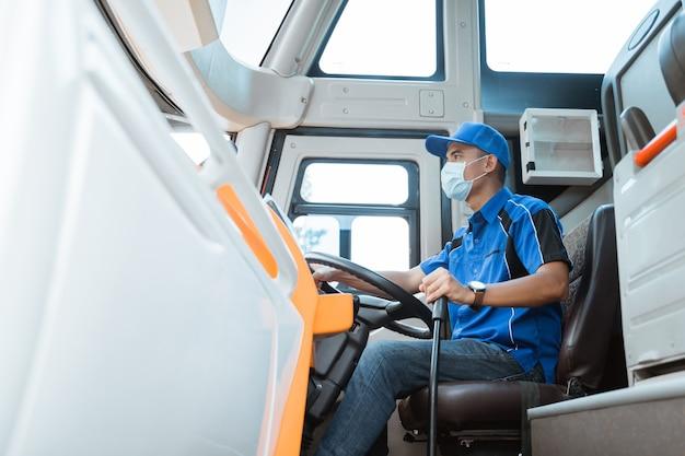 Primo piano del conducente maschio in uniforme e indossa una maschera mentre si tiene il volante e la leva del cambio nell'autobus