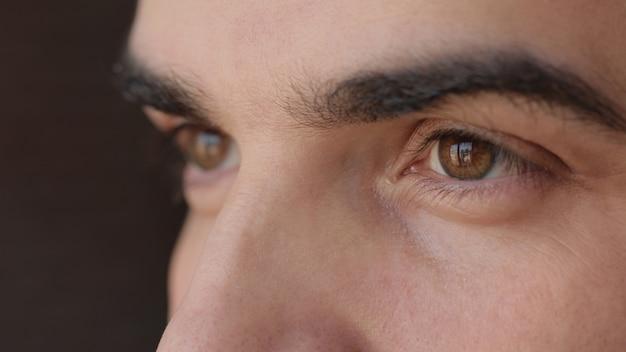 Primo piano del volto maschile. uomo attraente con occhi marroni e ciglia lunghe.