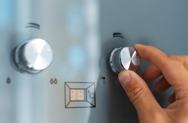Primo piano della mano maschio che regola la temperatura dello scaldabagno. caldaia a gas domestica moderna.