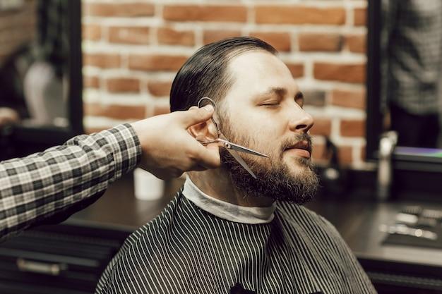 Una mano maschio del primo piano taglia la barba del cliente con le forbici