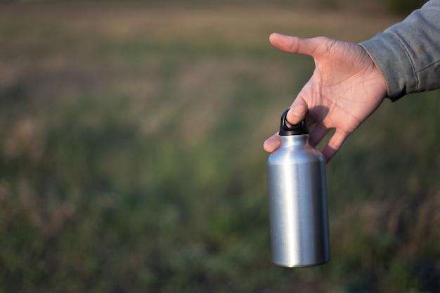 Chiuda in su della mano maschio che tiene la bottiglia di acqua termica di alluminio