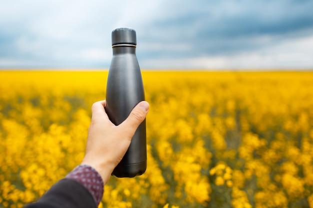 Primo piano della mano maschile che tiene una bottiglia di metallo eco grigio scuro sullo sfondo di un campo di colza sfocato.