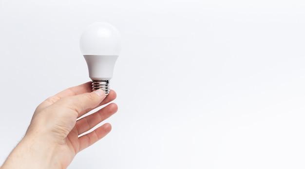Primo piano della mano maschio che tiene una lampadina di eco con lo spazio della copia. concetto di nuova idea.