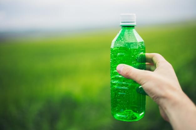 Primo piano della mano maschio che tiene la bottiglia di plastica verde spruzzata con acqua su sfondo sfocato all'aperto.