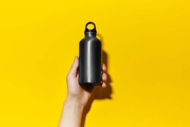 Primo piano della mano maschio che tiene la bottiglia di acqua termica riutilizzabile di alluminio di colore nero