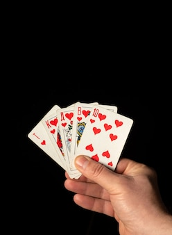 Chiuda sulla mano maschio che tiene le carte di scala reale mentre gioca a poker