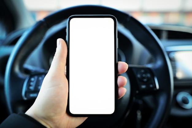 Primo piano della mano maschio che tiene smartphone con mockup bianco sullo schermo